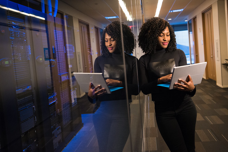 Image of African American women with computer in hand leaning against darkened window where her reflection and a supercomputer can be seen.